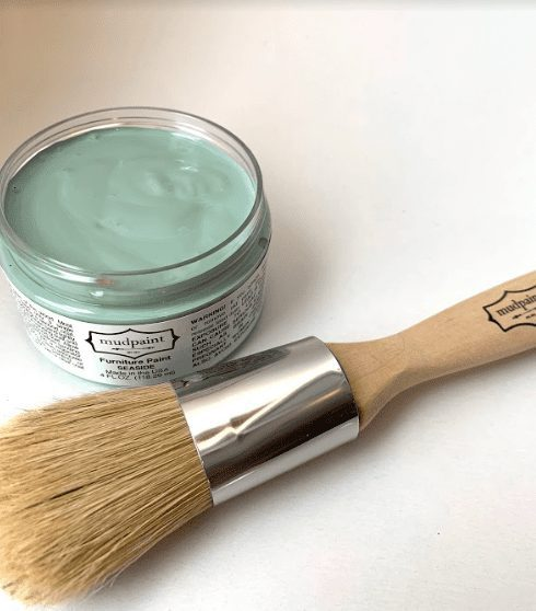open container of blue green clay furniture paint color lying next to a 1 inch natural bristle brush
