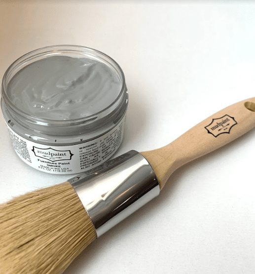 open container of gray clay furniture paint color lying next to a 1 inch natural bristle brush
