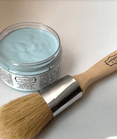 open container of light blue clay furniture paint color lying next to a 1 inch natural bristle brush