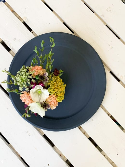 top down view of flowers and platter painted in dark navy clay furniture paint
