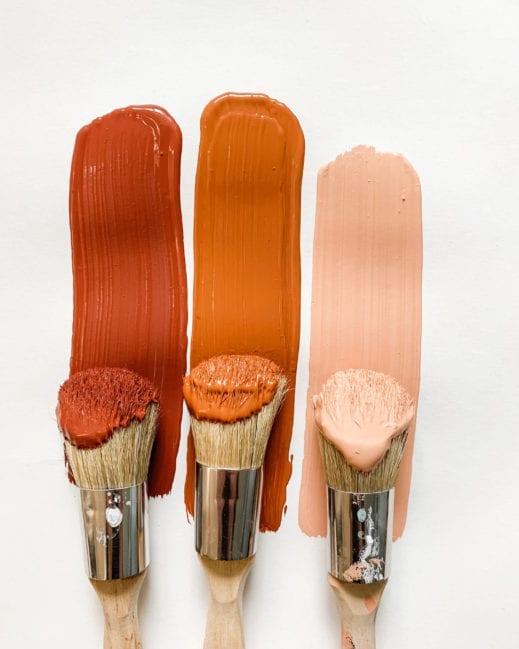 three paint brushes with various shades of orange, pink and red clay furniture paint