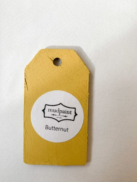 Small wooden tag hand painted with dark yellow clay furniture paint