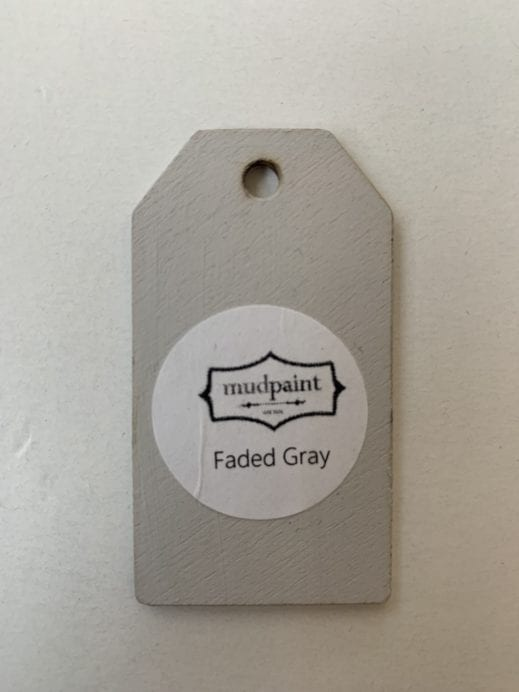 Small wooden tag hand painted with light gray clay furniture paint