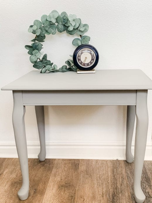 Small table with gray clay furniture paint and small wreath and clock