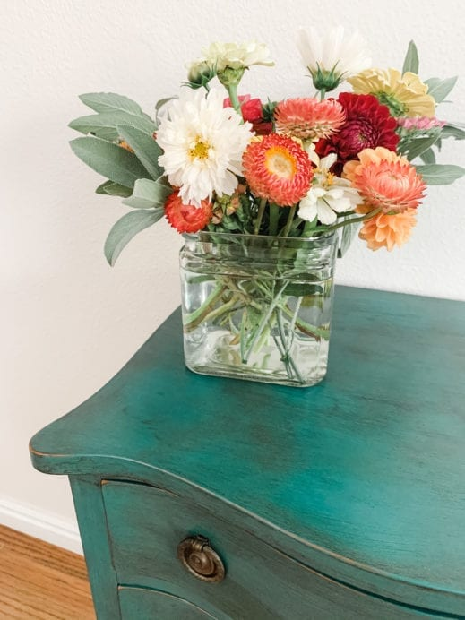 flowers on top of a small night stand painted with teal clay furniture paint and then distressed with black furniture wax
