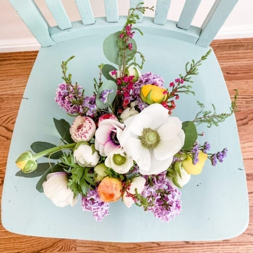 Flowers sitting on a chair painted with blue green clay furniture paint