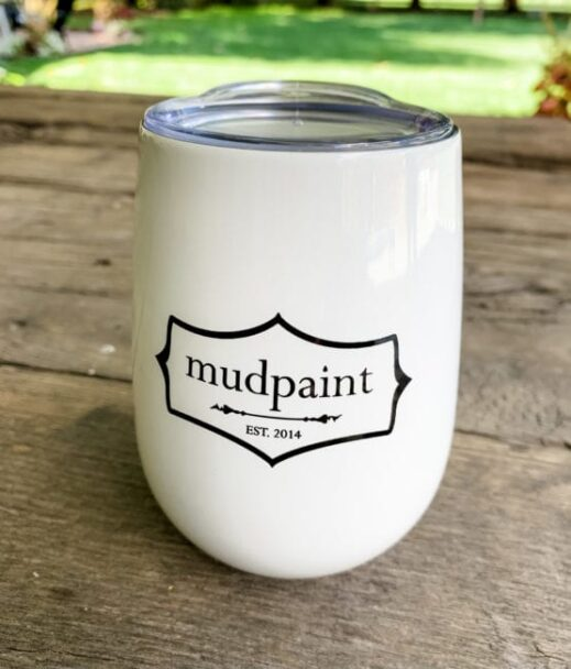 mudpaint branded coffee cup tumbler sitting on a wooden table