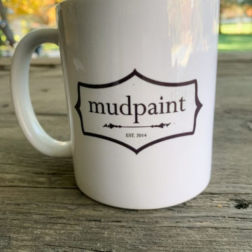 MudPaint coffee cup placed on a wooden table outside in the sunlight